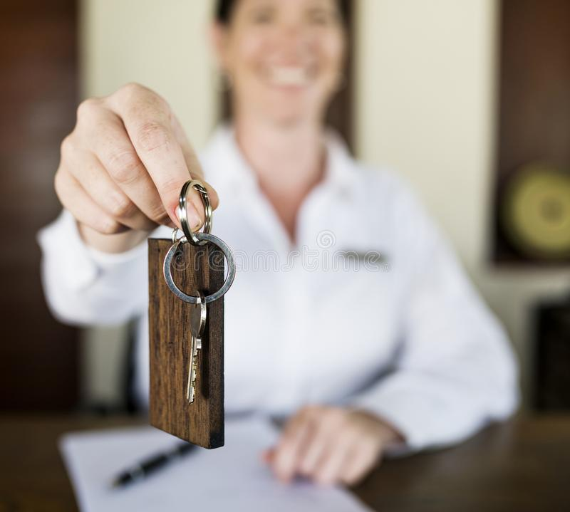 Receptionist handing room key to guest stock photography