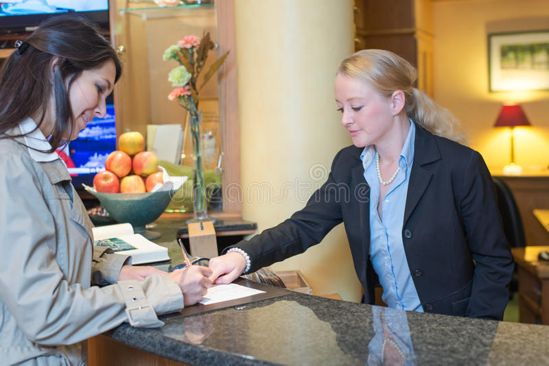 Receptionist helping a hotel guest check in. Smiling attractive young receptionist helping a hotel guest check in pointing to information on the form that needs stock photo