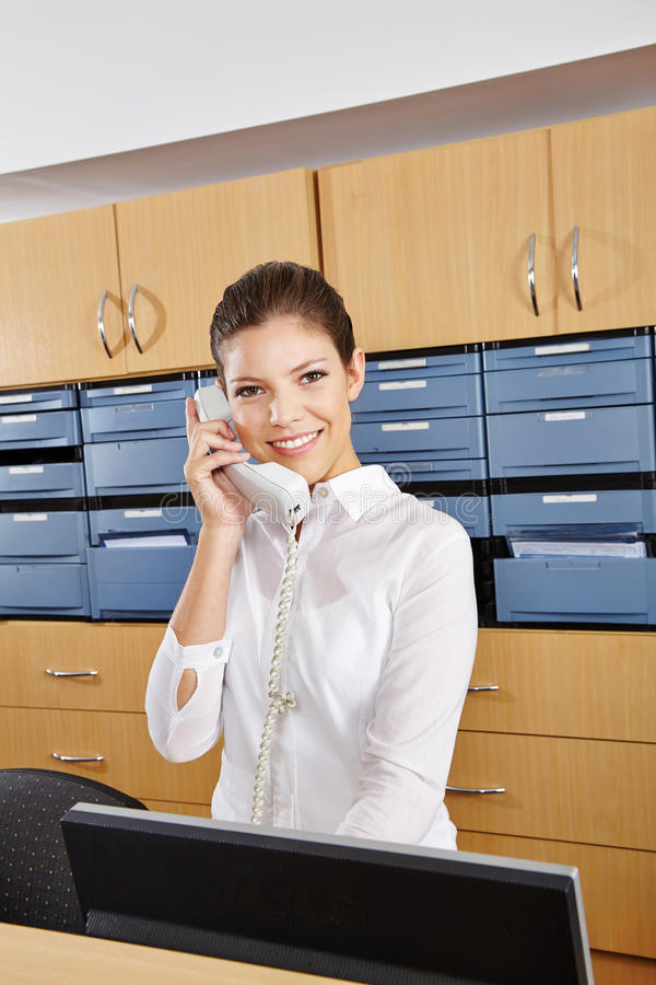 Receptionist in hospital taking call. Young receptionist in a hospital taking a phone call royalty free stock photography