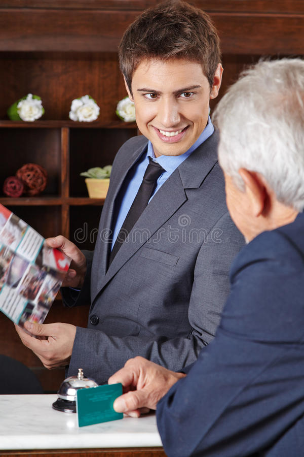 Receptionist in hotel giving brochure to guest. Receptionist in hotel giving brochure to senior guest stock photo