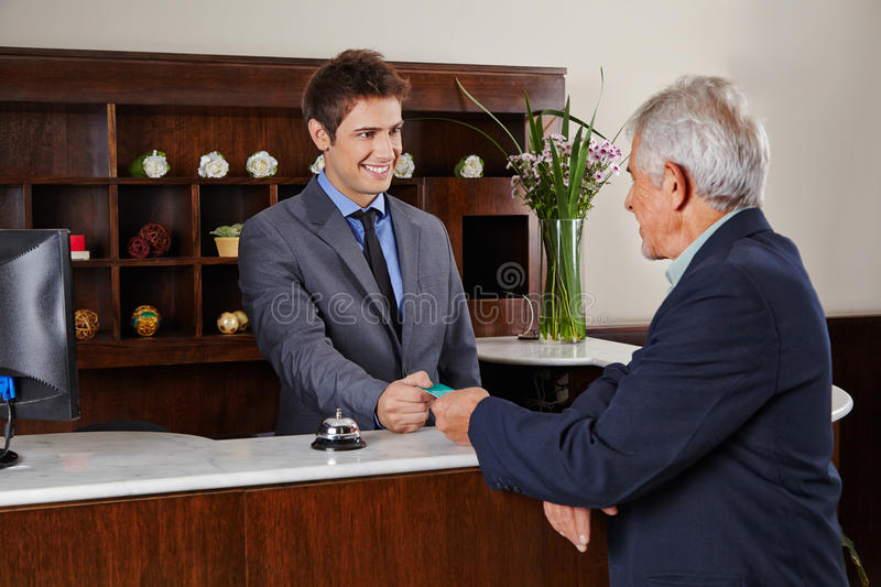 Receptionist in hotel giving key card to senior. Smiling receptionist behind counter in hotel giving key card to senior guest royalty free stock images