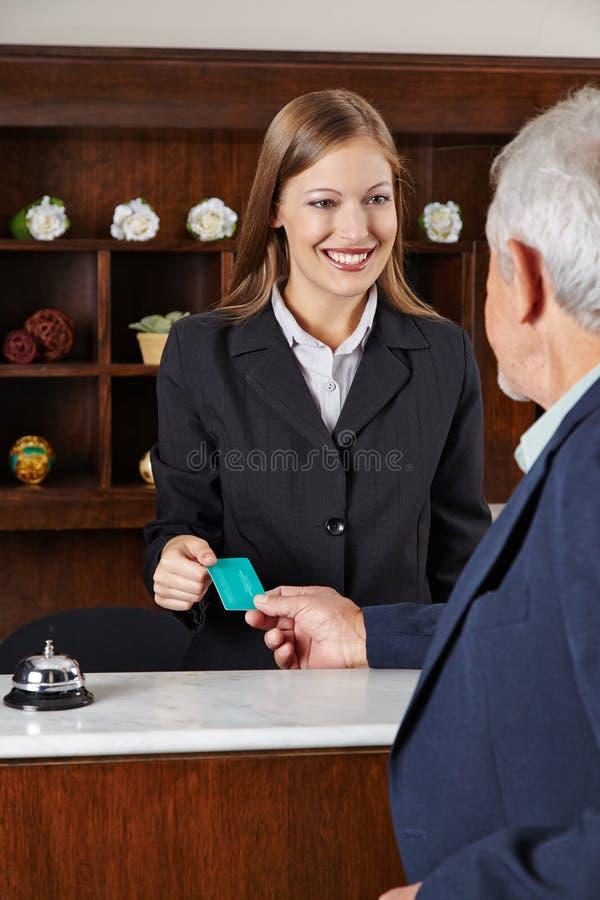 Receptionist in hotel greeting senior man. Smiling female receptionist in hotel greeting a senior man stock photos
