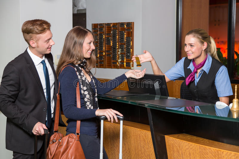 receptionist at hotel reception handing over key to guest or customer stock photo