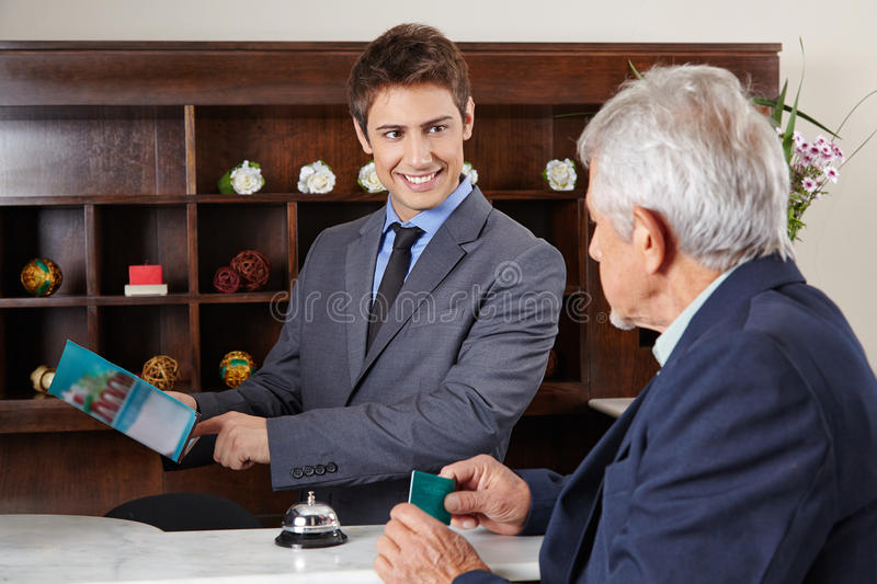 Receptionist in hotel showing city map stock images