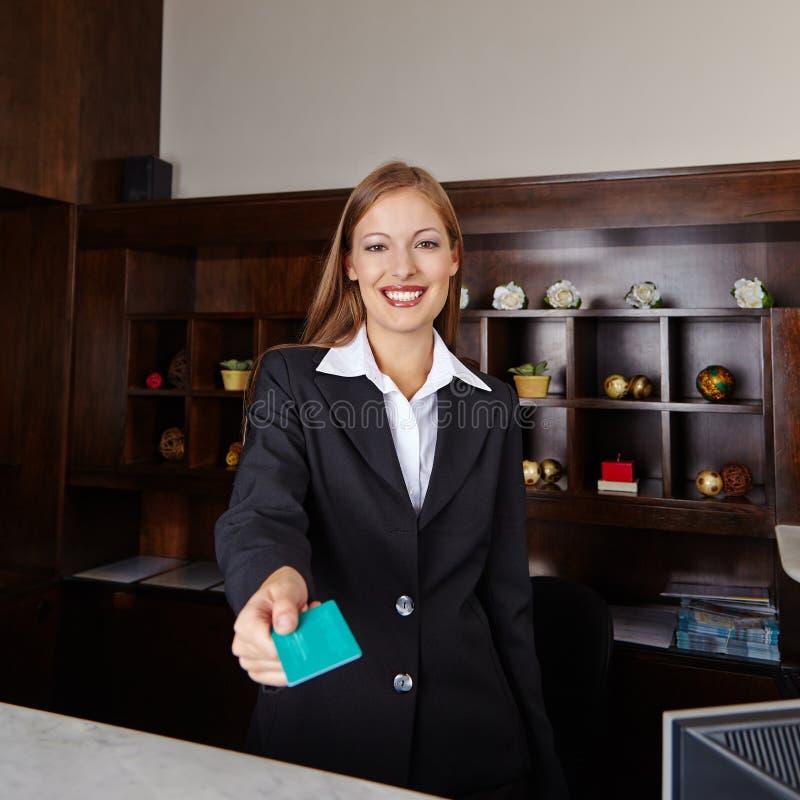 Receptionist nella carta chiave d'offerta dell'hotel fotografia stock libera da diritti