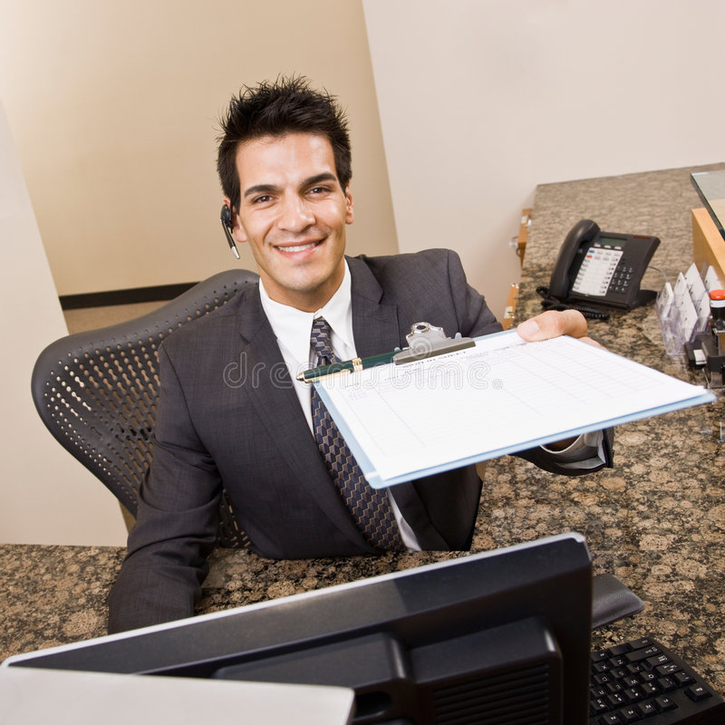 Download Receptionist Offering Clipboard And Pen Stock Photo - Image: 6603910