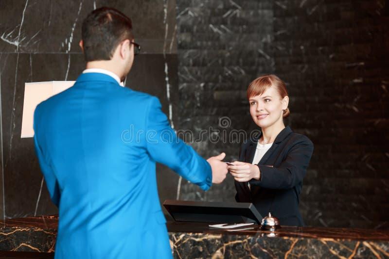 Receptionist på arbete bak räknaren arkivbilder