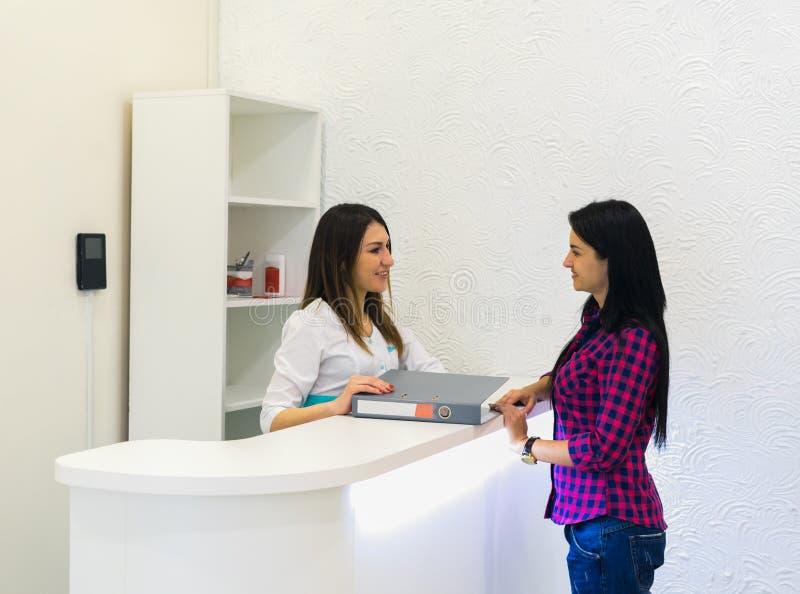 Receptionist på den medicinska kliniken med patienten royaltyfria bilder