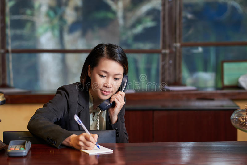 Receptionist on phone. Vietnamese receptionist taking notes when calling on the phone royalty free stock images