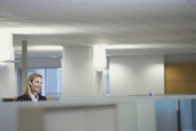 Receptionist At Reception Desk. Beautiful female receptionist at reception desk stock photography