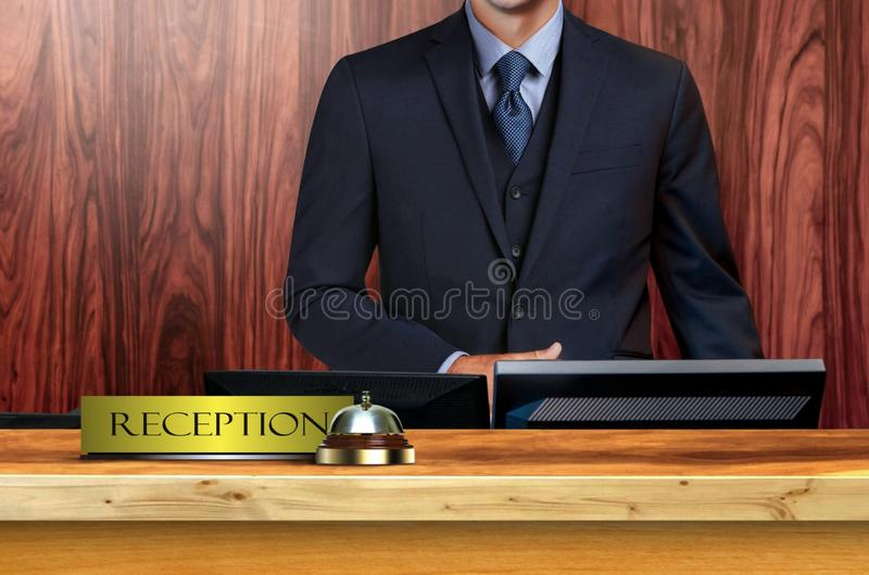 Receptionist at the reception front desk waiting to serve hotel guest. Male receptionist at the reception front desk waiting to serve hotel guest stock images
