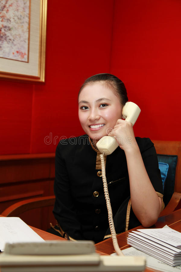 Receptionist or secretary. At work calling and smiling royalty free stock photography