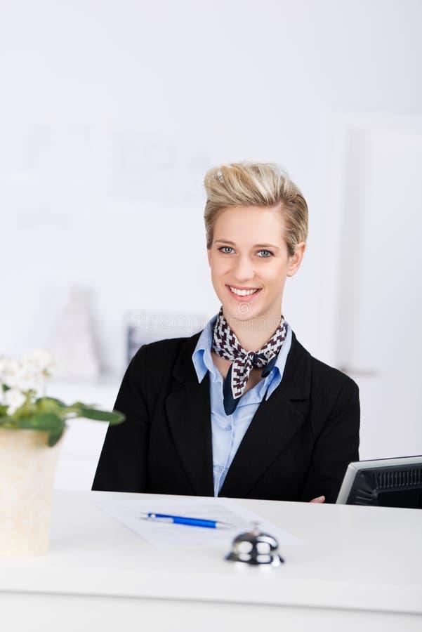 Receptionist Smiling At Desk. Portrait of confident receptionist smiling at desk stock photography