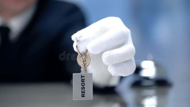 Receptionist som visar keychain med semesterortordet, lyxig egenskapshyra, closeup royaltyfri bild
