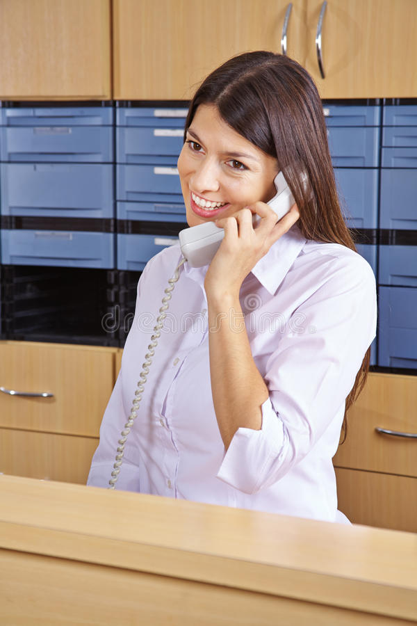 Receptionist taking phone call in hospital. Female receptionist taking phone call in hospital reception royalty free stock image