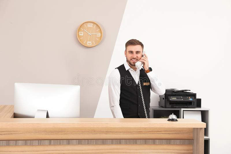 Receptionist talking on telephone at desk in hotel. Receptionist talking on telephone at desk in modern hotel stock image