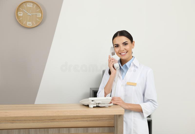 Receptionist talking on telephone at desk stock photography