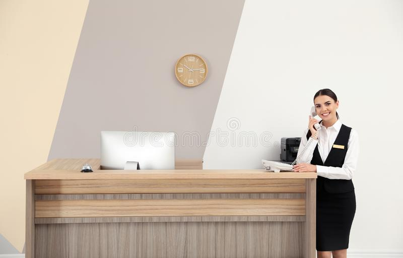 Receptionist talking on telephone near desk in hotel. Receptionist talking on telephone near desk in modern hotel stock photography
