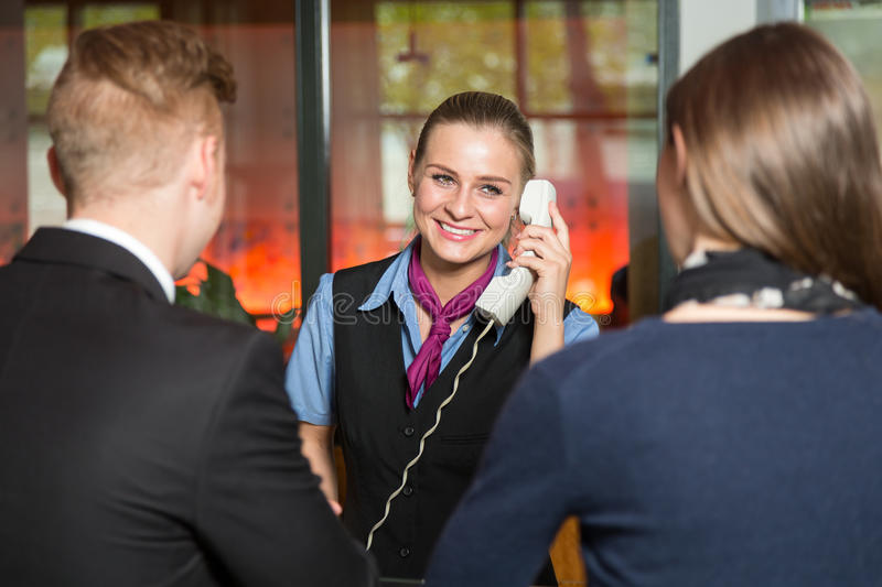 Receptionist with telephone assisting guests in hotel. Receptionist with telephone assisting guests in a hotel royalty free stock photography