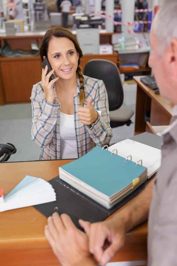 Receptionist on telephone making positive gesture to customer. Receptionist stock image