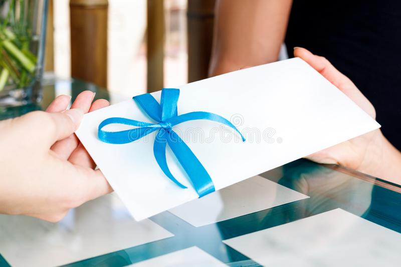 Receptionist woman gives certificate to visit of spa salon. Receptionist women gives gift certificate to young couple for visit spa salon royalty free stock photo