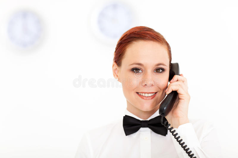 Receptionist working. Pretty young receptionist working at hotel reception royalty free stock image
