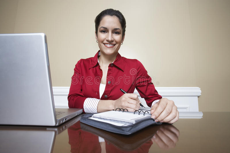 Receptionist Writing In Diary In Office. Portrait of a beautiful receptionist writing in diary beside laptop in office royalty free stock photos