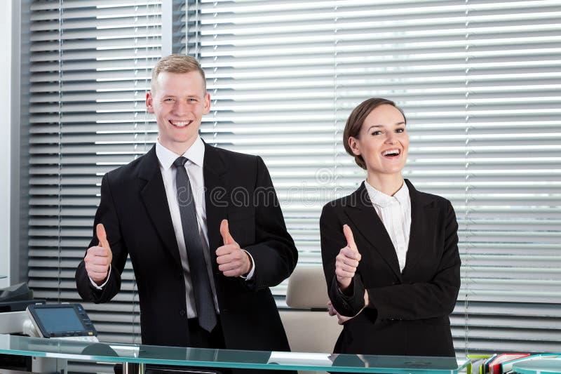 Receptionister som visar tummar, up tecknet royaltyfri foto