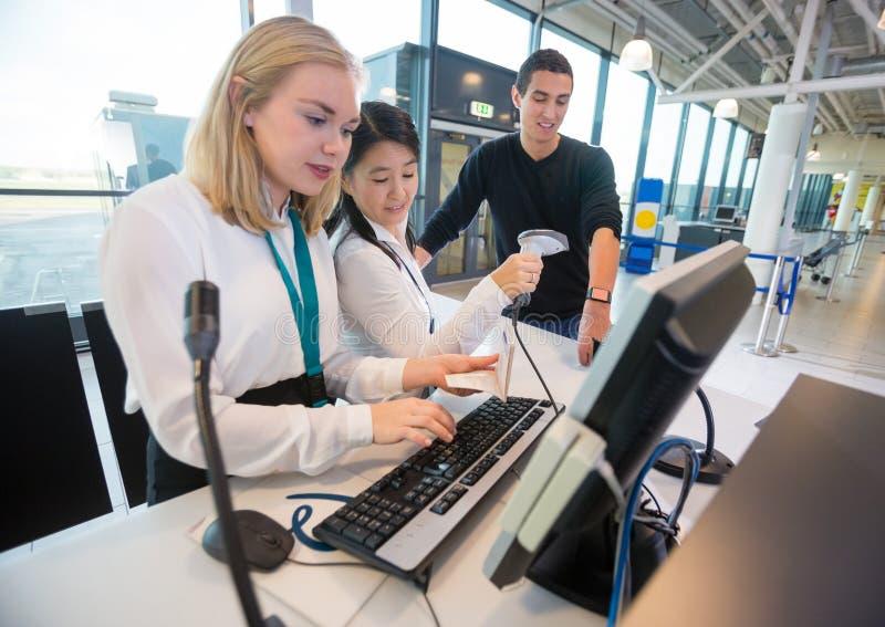 ReceptionistWith Passport Using dator medan kollega Scanni royaltyfria foton
