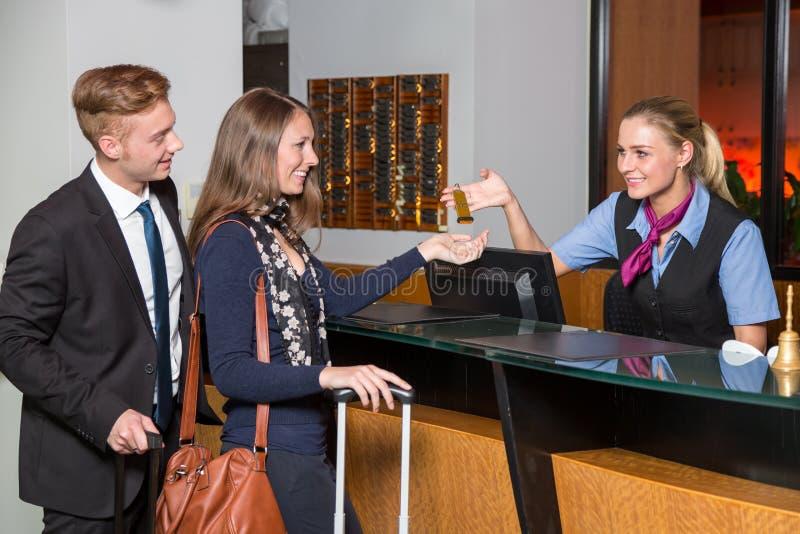 Receptionnist bij hotelontvangst het overhandigen sleutel tot gast of cus stock foto