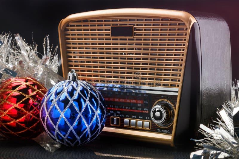 Receptor de radio en estilo retro con las decoraciones de la Navidad en fondo negro imágenes de archivo libres de regalías