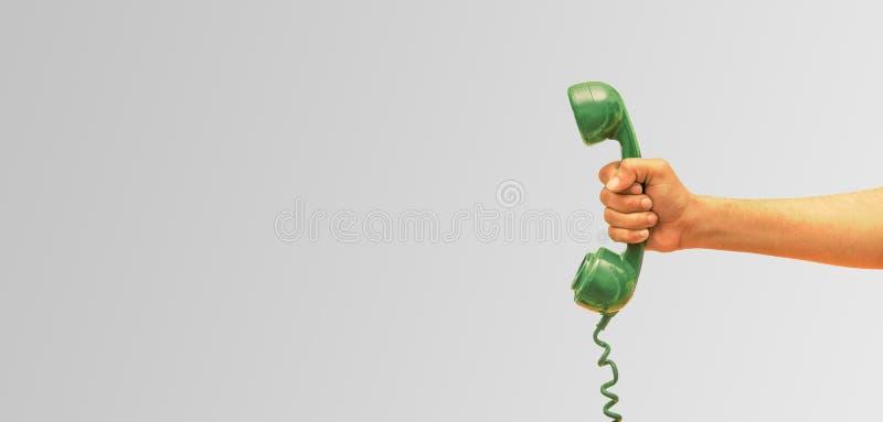 Receptor velho do telefone à disposição, homem de negócios que guarda o receptor velho do telefone, fundo da bandeira fotos de stock royalty free
