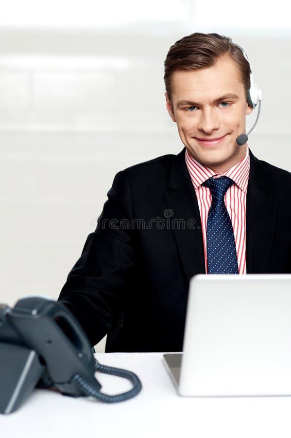 Receptores de cabeza que desgastan ejecutivos masculinos y sonrisa imagen de archivo libre de regalías
