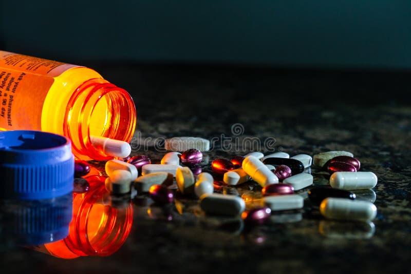 Receptpreventivpillerflaska med åtskilliga preventivpillerar och kapslar som ut spiller royaltyfria foton