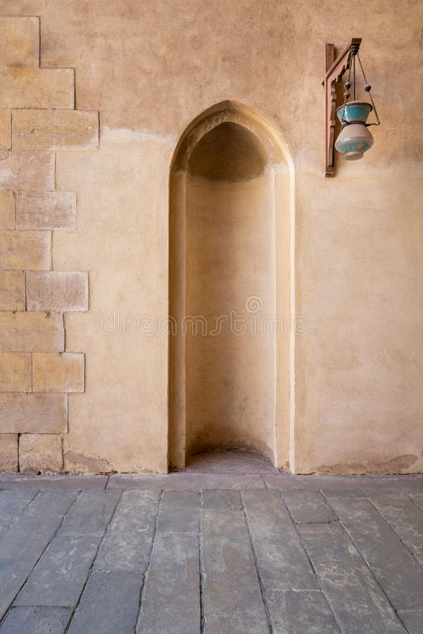 Recessed frame, niche and glass street lantern hanged on a wooden pole in an old stone bricks wall royalty free stock photography