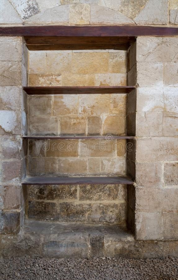 Recessed frame, Niche with wooden shelves in an old grunge stone bricks wall stock images