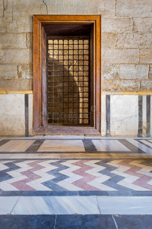 Recessed wooden window with decorated iron grid over stone bricks wall and decorative colorful floor. At public historic mosque of Sultan Barquq, El Moez Street stock photo