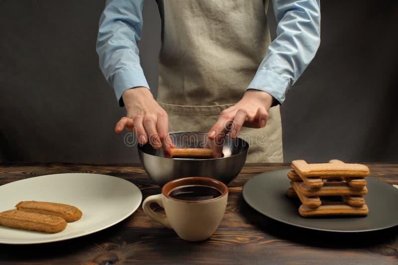 Receta de cocinar de un postre del tiramisu, sexto de la parte: 'Impregnación de la galleta en café ' imágenes de archivo libres de regalías