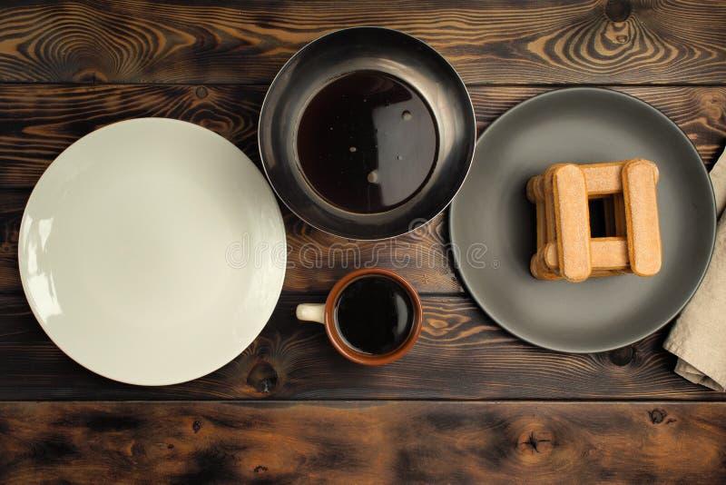 Receta de cocinar de un postre del tiramisu, sexto de la parte: 'Impregnación de la galleta en café ' fotografía de archivo