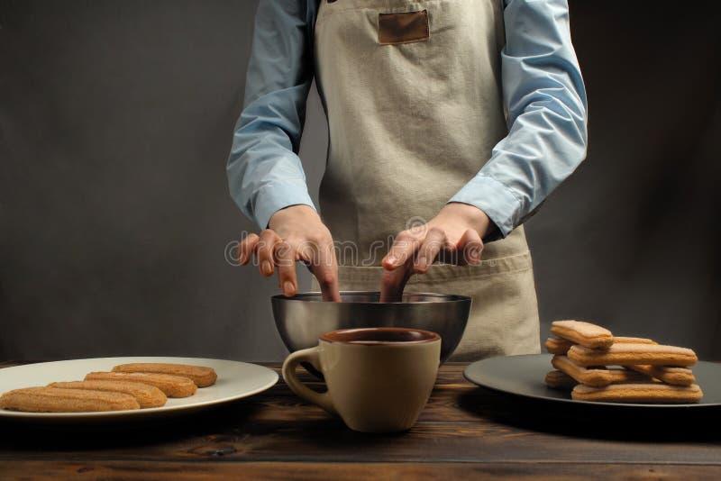 Receta de cocinar de un postre del tiramisu, sexto de la parte: 'Impregnación de la galleta en café ' fotos de archivo