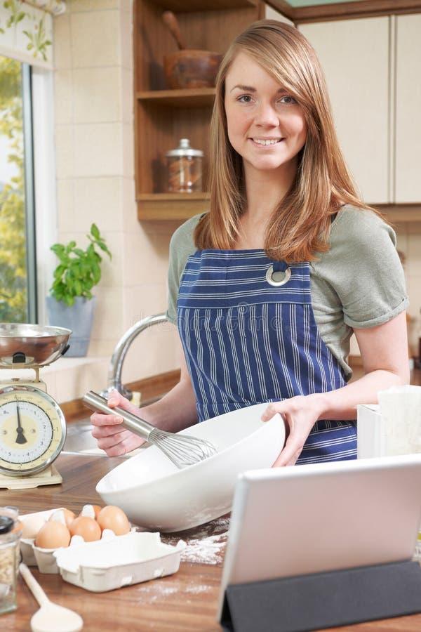 Receta de cocinar y de siguiente de la mujer en la tableta de Digitaces fotos de archivo libres de regalías
