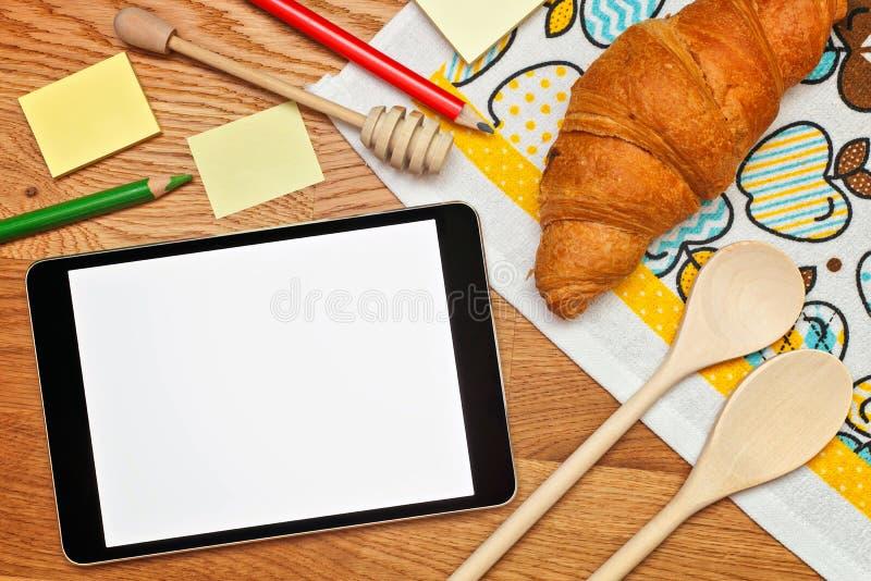 Receta de Digitaces en la tableta en la cocina para preparar la opinión superior del desayuno fotos de archivo