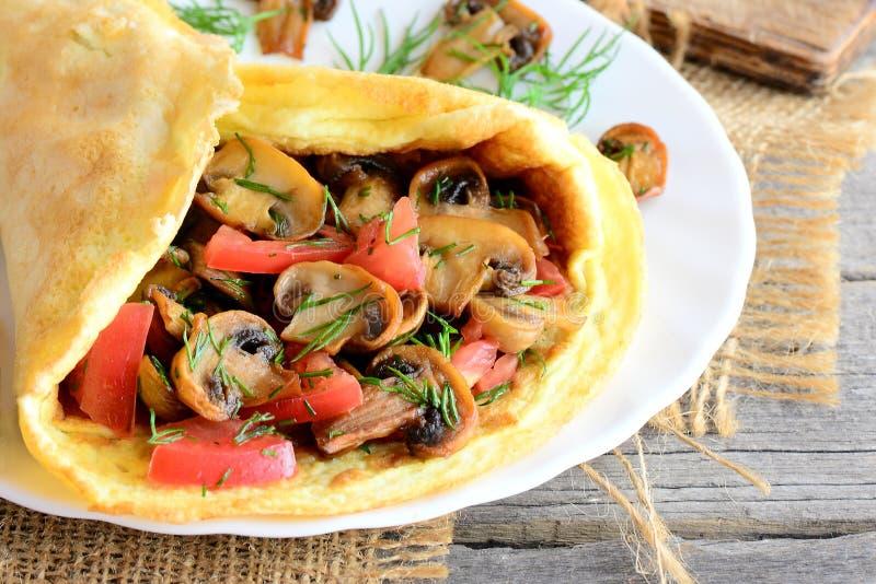 Receta fácil de la tortilla de las setas Tortilla hecha en casa rellena con las setas, los tomates y el eneldo en una placa y un  foto de archivo