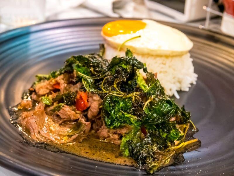 Receta famosa popular picante tailandesa del arroz frito de la carne de vaca de la albahaca de la comida con el huevo encendido K foto de archivo libre de regalías