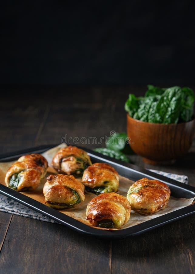 Receta hecha en casa de los cruasanes rellenos con espinaca y ricotta en el papel de la hornada en plato de la hornada con el cue foto de archivo libre de regalías