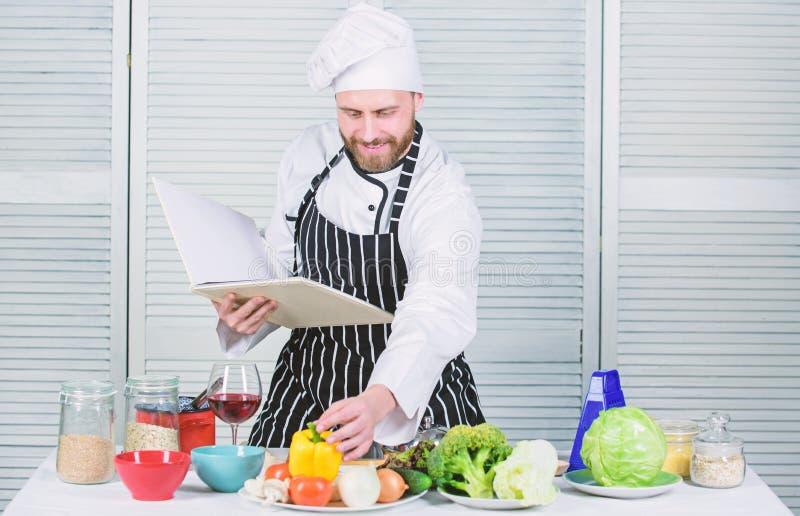 Recetas de la familia del libro ?ltima gu?a de cocinar para los principiantes Seg?n receta Cocinero barbudo del hombre que cocina fotografía de archivo