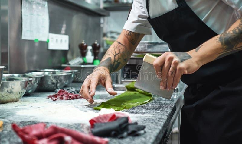 Recette secrète Photo cultivée des mains du chef avec des tatouages coupant la pâte sur la table de cuisine avec de la farine pou images libres de droits