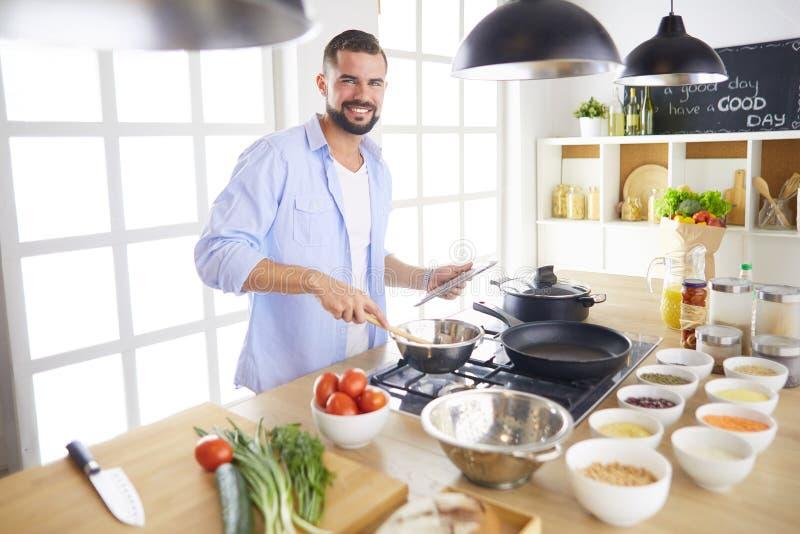 Recette suivante d'homme sur le comprimé numérique et faire cuire la nourriture savoureuse et saine dans la cuisine à la maison photographie stock libre de droits