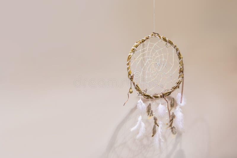Receveur rêveur avec les plumes blanches sur un fond beige dans l'intérieur images libres de droits