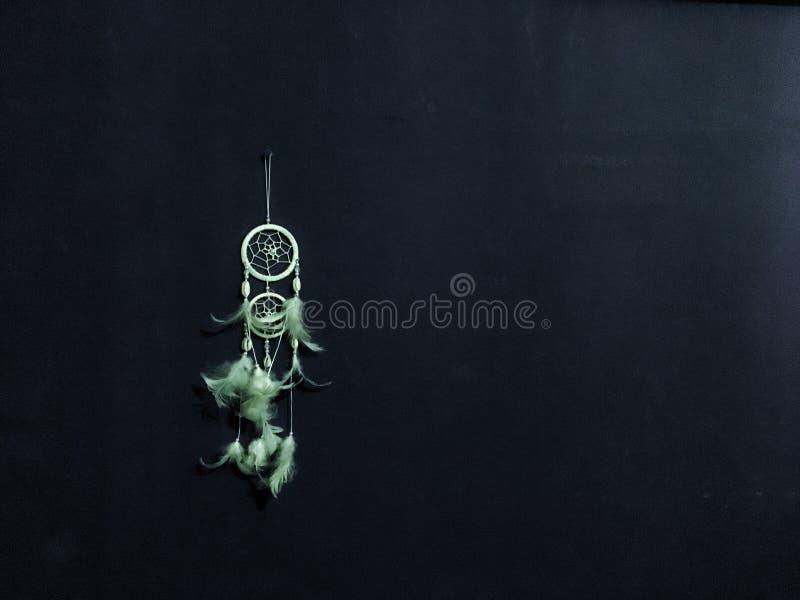 Receveur rêveur blanc avec le coup de plume sur le clou sur le mur noir photo stock
